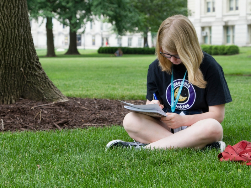 A student sitting in the grass while working on their writing at the Summer Residential Program